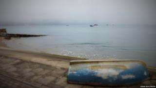View of a beach looking out towards the sea. There is an upturned boat in the foreground. The sea is calm with a few boats in the misty distance