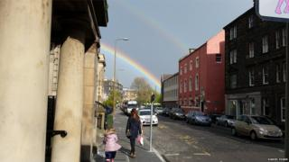 A double rainbow appears across a street. A woman and girl walk along the pavement, there are a few cars parked up. The sky is clear and a blue-grey