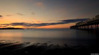 A beach sunrise. The sea is misty and cloud-like. The sky is hazy and orange and yellow toned