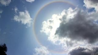 Ice halo in a blue sky. The sun is hidden behind a cloud