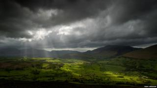 Grey clouds move across a countryside landscape