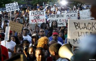 Protesters listen during a rally against what is being described as police brutality in McKinney, Texas June 8, 2015