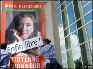 "A poster in France of Ingrid Betancourt is covered over with a sign ""Free at last"""
