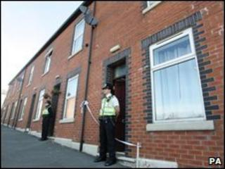 Police stand guard outside two houses on Percival Street in Blackburn