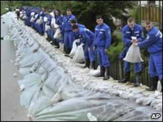 Police academy students load sandbags onto a broken dam to protect homes from flooding in north-eastern Hungary, 18 May 2010
