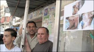 Residents of Ketermaya stand next to a poster showing the a murder victim's body