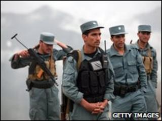 Afghan policemen gather near the area where a plane is believed to have crashed, on May 17, 2010