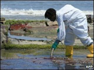 A BP clean-up crew worker cleans oil from a beach in Louisiana, 24 May