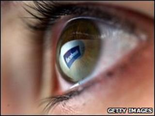 An eyeball reflecting the Facebook logo