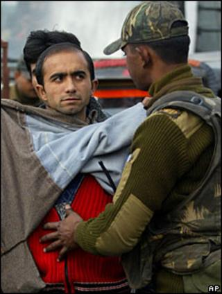 Man being searched by security forces in Indian-administered Kashmir