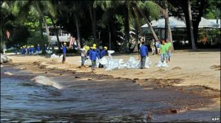 Workers clean oil on a beach in Singapore (27 May 2010)