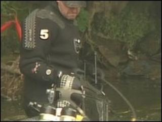 A police diver hands the large, black suitcase to a waiting officer