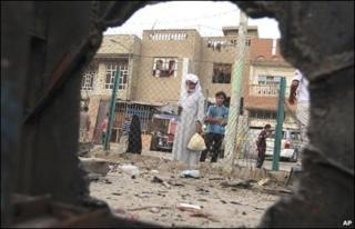 Iraqis inspect a bomb blast site