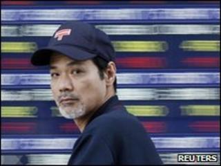 Man walking past electronic stock board in Tokyo