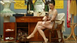 """Royal Ballet Principal Mara Galeazzi looks at a ballet shoe, part of a recreation of Margot Fonteyn""""s dressing room, which will form part of Invitation to the Ballet: Ninette de Valois and the Story of the Royal Ballet"""