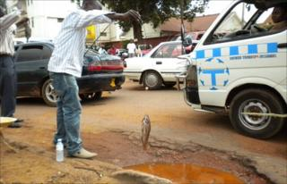 Ugandan protesters fish in potholes in the Ugandan capital, Kampala