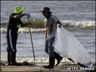 Workers hired by BP clean a beach of oil in in Grand Isle, Louisiana