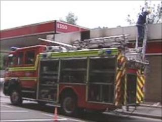 A firefighter dampens down at the petrol station in Mountain Ash