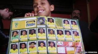 Boy holds an album he has bought and filled with the Brazilian team stickers