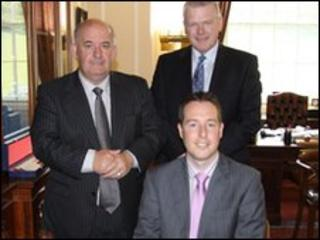 Mr Paul Givan (seated) with Speaker William Hay and the Director General Trevor Reaney after signing the Roll of Members