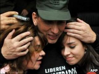 Former hostage Gen Luis Mendieta embracing wife and daughter