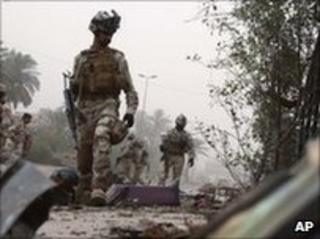 Iraqi soldiers inspect scene of car bomb explosion