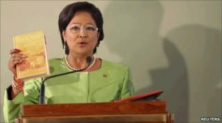 Ms Persad-Bissessar holds the Gita as she takes the oath of office in Port of Spain 27/05/2010