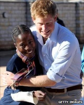Prince Harry hugs a child affected by HIV-Aids