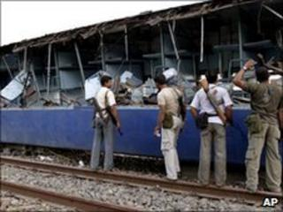 police walk past remains of shattered carriage