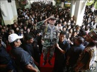Supporters hold up a cutout of Maj Gen Khattiya Sawasdiphol during his cremation ceremony