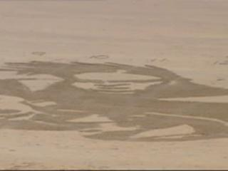 The image takes shape on the beach