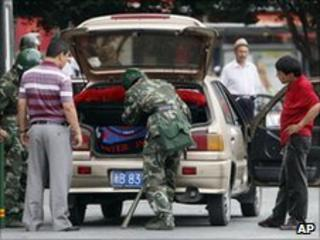 Chinese police search a car in Urumqi on 14 July 2009