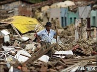 Man stands near destroyed house in Palmares city, Alagoas, Brazil, on 23/6/2010