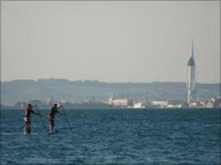 Stand-up paddlle surfing near Portsmouth's Spinnaker Tower