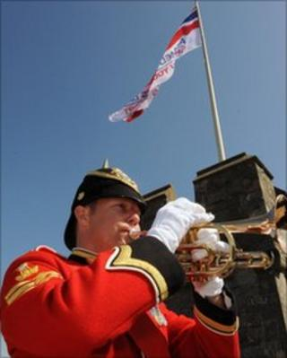 Bugler from the Royal Welsh Band plays as the Armed Forces Day flag is raised in Cardiff