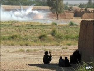 Afghan civilians look on as a British army mortar explodes in Helmand, June 2010