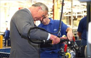 The Prince of Wales works on a turbocharger, assisted by Anthony Hookings, at the Ford engine plant near Bridgend. (Photo: David Jones/PA Wire)