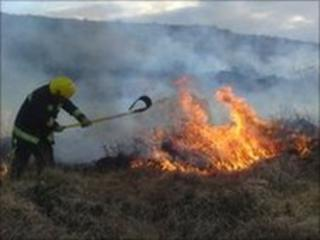 Fireman with beater at gorse fire