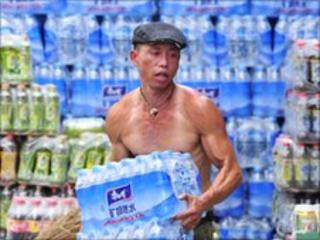 A migrant worker carries bottles of drinking water at a store in Nanjing, Jiangsu province (18 June 2010)