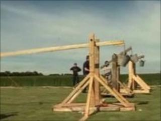Trebuchets launch eggs at a human target