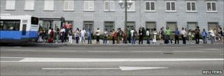 Commuters queue for the bus during a metro strike in Madrid, 29 June 2010