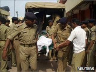 Police officers carry the body of their colleague outside a hospital in Raipur, in Chhattisgarh, on June 30, 2010