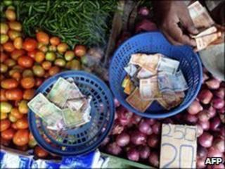 A Sri Lankan stallholder counts his takings in a market in Colombo