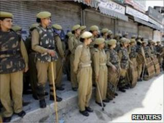 Policewomen stand near closed shops during a curfew in Srinagar on July 1, 2010