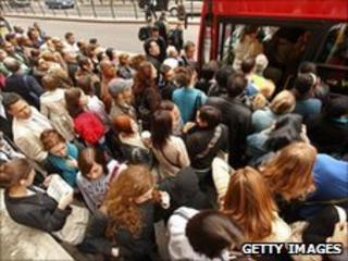 A crowd of people getting on a bus