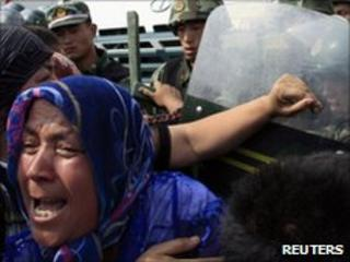 A crowd of angry locals confront security forces on a street in the city of Urumqi