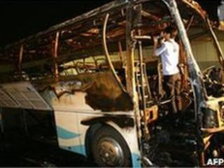Official inspects bus gutted by fire in Jiangsu, 5 July 2010