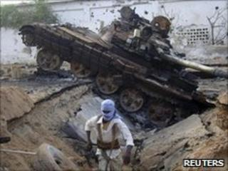 Rebel fighter next to African Union tank