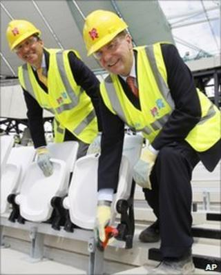 IOC President Jacques Rogge, right, and Sebastian Coe, chairman of the London Organising Committee for the Olympic Games help install the 2012th seat during a visit to the Olympic Stadium in London