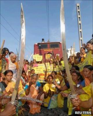 Protesters hold swords and sticks as they block a railway track in Patna, Bihar, on July 5, 2010